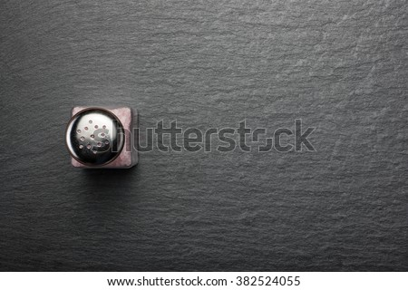 salt shaker with pink Himalayan salt on black stone background, view from the top - stock photo