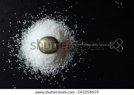 Salt with a spoon on a dark background - stock photo