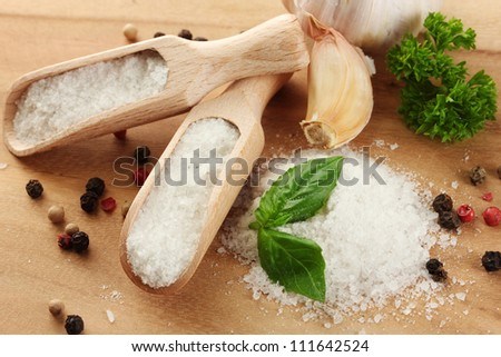 salt with fresh basil and parsley, garlic and pepper on wooden table