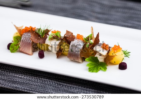 Salted and marinated herring on creamy cheese, beer and black bread chips, potatoes and red caviar - stock photo