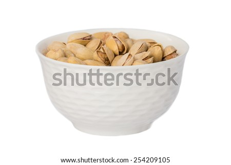 Salted and roasted pistachio nuts in bowl isolated on white background - stock photo