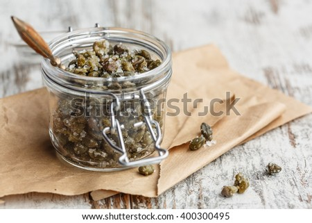Salted capers in glass jar - stock photo