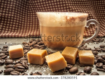 Salted Caramel Latte. Salted caramel latte surrounded by coffee beans, caramels, and sea salt. Shot from a side view with selective focus and a rustic gingham background. - stock photo