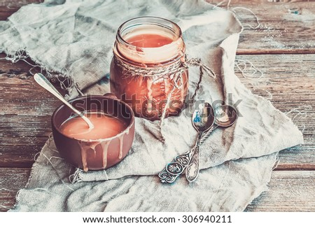 Salted caramel sauce in a rustic glass jar and brown ceramic cup on a wooden desk - stock photo