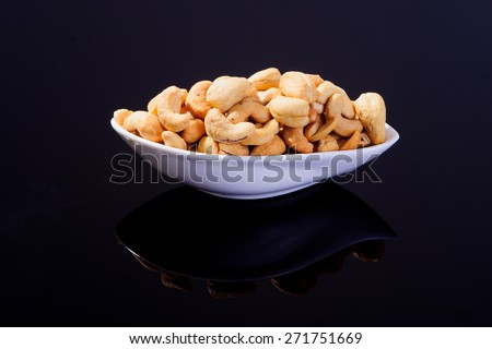 Salted Cashew Nuts in a white plate on a black background - stock photo