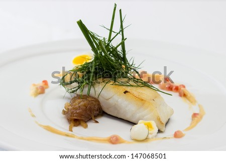 Salted cod brushed, served with caramelized onion quail eggs poached for 2 minutes, butter-wine sauce, caviar and dill - stock photo