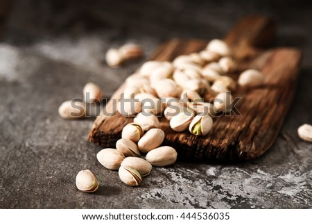 Salted dried roasted pistachios nuts with shell and salt. The rustic style on the wooden background.  - stock photo