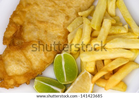 Salted french fries with large serving of fried fish with lemon and lime wedges - stock photo
