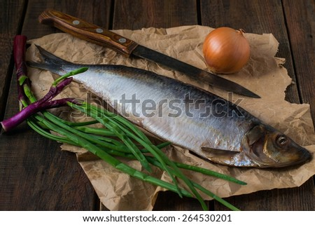 Salted herring on the wrapping paper, knife, onions and green onions on a wooden background. Selective focus - stock photo