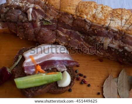 Salted Lard, Raw Pork with Spices on Wooden Cutting Board Studio. Fresh Meat. Bacon sandwich with garlic and cucumber.  - stock photo