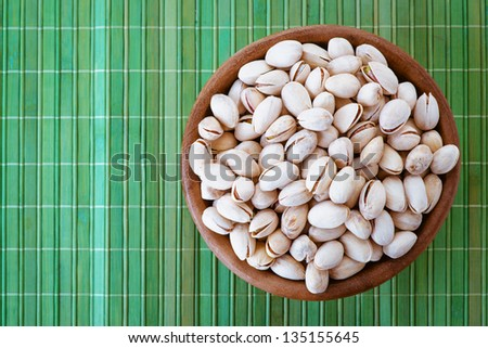 Salted peanuts in wooden bowl on green bamboo tablecloth. - stock photo
