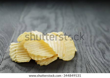 salted potato ships on old wooden table, selective focus - stock photo