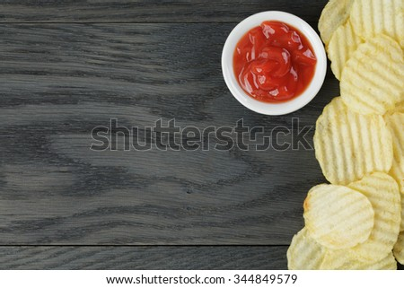 salted potato ships on old wooden table, top view - stock photo