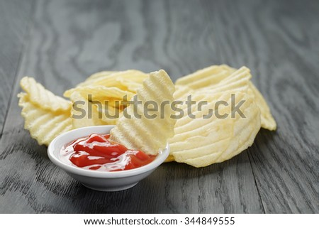 salted potato ships with sauce on old wooden table, selective focus