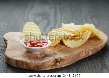 salted potato ships with sauce on old wooden table, selective focus - stock photo