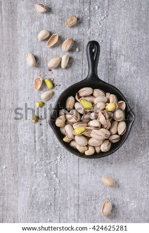 Salted roasted pistachios nuts with shell and salt  in black small cast-iron pan over white wooden textured background. Top view - stock photo
