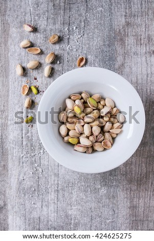Salted roasted pistachios nuts with shell and salt  in white ceramic plate over white wooden textured background. Top view. With copy space - stock photo