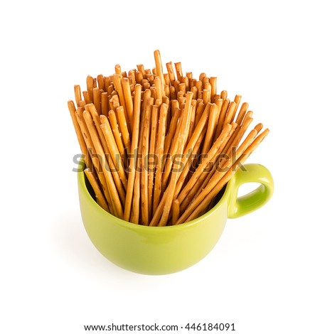 salted sticks in green cup isolated on white background - stock photo