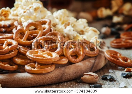 Salted straws in the shape of pretzels, popcorn and other salty snacks, junk food, snacks, for beer or cola, old wooden background, selective focus - stock photo