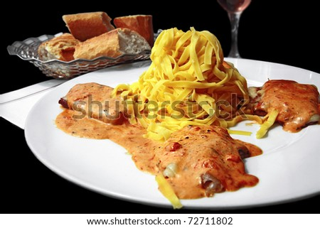 Saltimbocca alla Romana: Three small veal scaloppini stuffed with Parma ham & cheese topped with creamy tomato sauce with herbs. Served with tagliatelle pasta. On black background. - stock photo