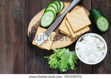Saltine crackers on a wooden board, lettuce, cucumber and ricotta in a jar topped with a knife on a cracker  - stock photo
