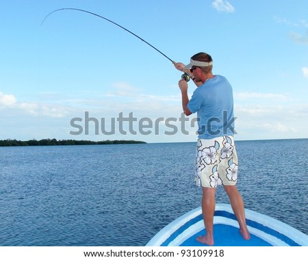 Saltwater fly fishing for bonefish - Fighting a big fish in the ocean off the front of a boat - stock photo
