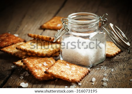 Salty cracker and sea salt in a pot on a dark wooden background, toned image, selective focus - stock photo