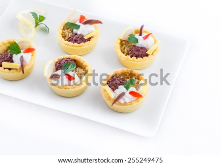 Salty mini tarts stuffed with green and black olive paste - stock photo