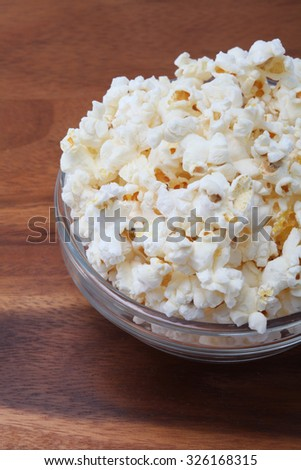 salty popcorn in a transparent bowl on the table ready to serve  - stock photo
