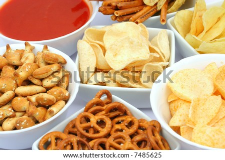 Salty snacks in square bowls with salsa dip sauce - stock photo