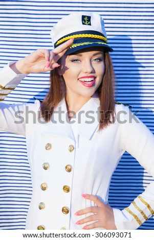 Saluting happy young attractive woman wearing marine captain uniform over stripy background - stock photo