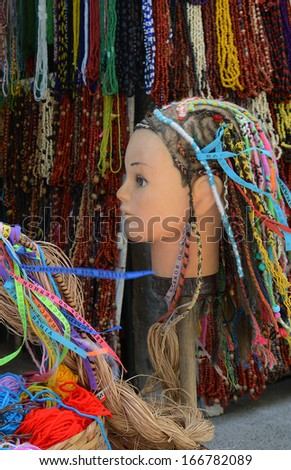 "SALVADOR, BAHIA, BRAZIL:09 DEC 2013: a doll's head displays the traditional ornament for hair ""Terere"" in a store at Pelorinho square on 09th Decenber 2013,in Brazil. - stock photo"