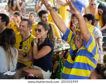 Salvador, Bahia, Brazil - June 28: Cheerful Brazil fans watching football match on TV at a bar in Salvador, Bahia, Brazil. - stock photo