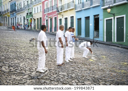 SALVADOR, BRAZIL - OCTOBER 13, 2013: Group of men wearing white perform a religious ceremony in a plaza in the historic center of Pelourinho. - stock photo