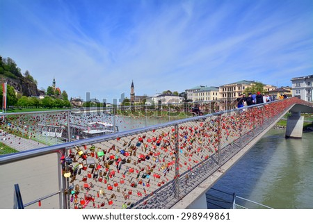 salzburg, austria - april 25: bridge with love locks and the salzach river in salzburg, austria. shot taken on april 25th, 2015 - stock photo
