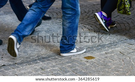 Salzburg, Austria - October 12, 2015, People walk next to a stumbling stone. These brass plaques are installed in the pavement of the last address of those killed or displaced by the Nazis. - stock photo