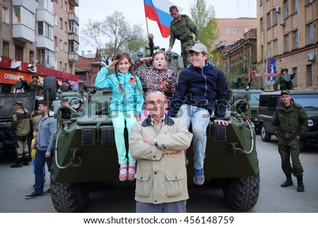 SAMARA - MAY, 6, 2015: Boy, man and two girls (with model releases) pose on armored vehicle in Samara during military celebration. Red Square is not affected by military equipment on parade May 9th - stock photo