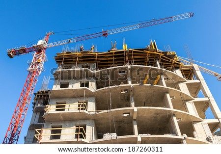SAMARA, RUSSIA - APRIL 13, 2014:Tall building under construction with crane against a blue sky - stock photo