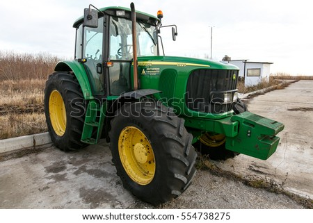 Samara, Russia - CIRCA 2016: John Deere tractor on the farm in Russian countryside.