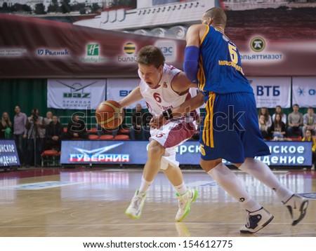 SAMARA, RUSSIA - DECEMBER 17: Dmitry Kulagin of BC Krasnye Krylia with ball tries to go past a BC Khimki player on December 17, 2012 in Samara, Russia. - stock photo