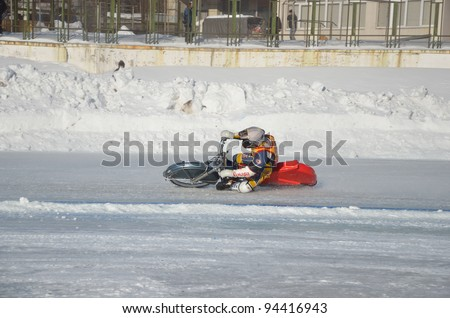 SAMARA, RUSSIA - JANUARY 29: Racing on ice, the unknown driver of a motorcycle with spikes rotates with a large slope on one knee on the ice speedway Championship January 29, 2012 in Samara, Russia