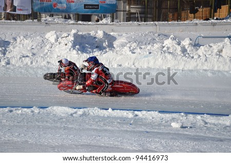 SAMARA, RUSSIA - JANUARY 29: Racing on ice, two unknown driver on a motorcycle with spikes turnabout with a large slope on knee, ice speedway Championship January 29, 2012 in Samara, Russia
