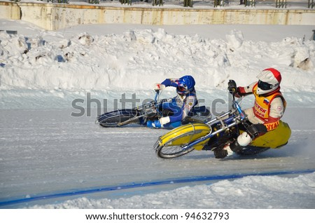 SAMARA, RUSSIA - JANUARY 29: Two rival motorcyclists blue A. Vitrik, red N. Toloknov on corner exit icy track, ice speedway Cup of Russia January 29, 2012 in Samara, Russia