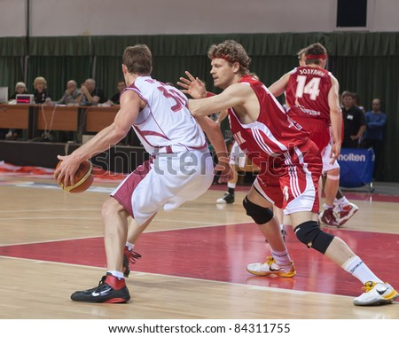 SAMARA, RUSSIA - JUNE 14: Andrey Trushkin of BC Krasnye Krylia with ball tries to go past a BC Spartak player on June 14, 2011 in Samara, Russia.