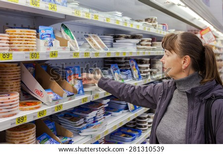 SAMARA, RUSSIA - OCTOBER 4, 2014: Young woman choosing food produces at shopping in supermarket store Magnit. Russia's largest retailer - stock photo