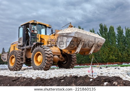 SAMARA, RUSSIA - SEPTEMBER 28, 2014: Heavy bulldozer loading and moving gravel on road construction site - stock photo