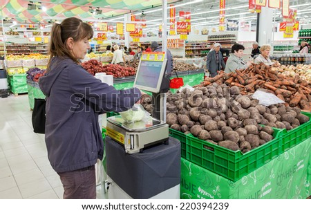 SAMARA, RUSSIA - SEPTEMBER 23, 2014: Young woman weighing vegetables on electronic scales in produce department of the Magnit store. Russia's largest retailer - stock photo