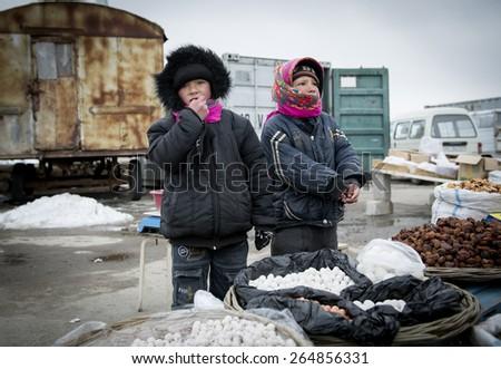 SAMARQUAND REGION, UZBEKISTAN - MARCH 14, 2015: Roadside bazaar. Children sell traditional Uzbek food. - stock photo