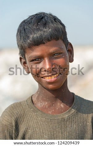 SAMBHAR, INDIA - NOV 19: Portrait of an unidentified indian child in salt farm on Nov 19, 2012 in Sambhar, India. It is India's largest saline lake where salt has been farmed for a thousand years. - stock photo