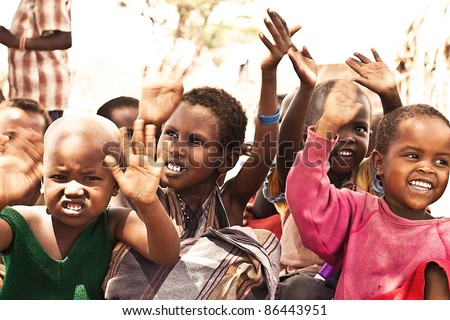 SAMBURU, KENYA - NOVEMBER 8: group of African unidentified kids, 3 to 6 years old, with hands up at outdoor school on November 8, 2008 in tribal village near Samburu National Park Reserve, Kenya. - stock photo